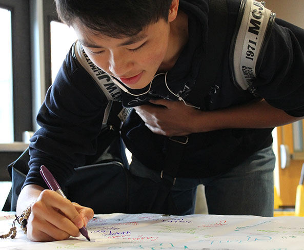 Junior Haoyu Wang signs a pledge to promote kindness following the assembly. Students who wanted to make a commitment to Rachel's Challenge signed the banner which now hangs in the school.