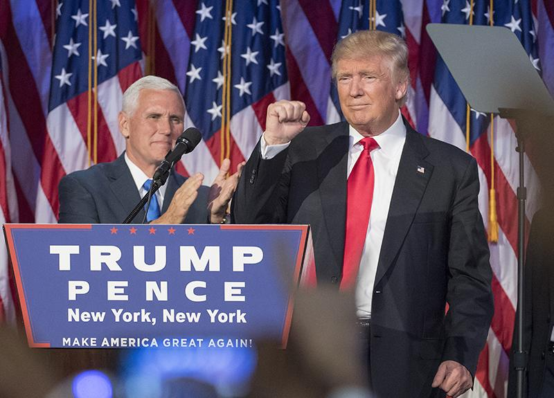 President-elect Donald Trump pumps his fist, with running mate Mike Pence standing by, following a speech to his supporters after winning the election at  the Election Night Party at the Hilton Midtown Hotel in New York City on Wednesday, Nov. 9, 2016.