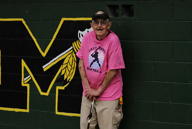 "Ray Jones, appropriately dubbed Manteo's ""superfan,"" supports the softball team."