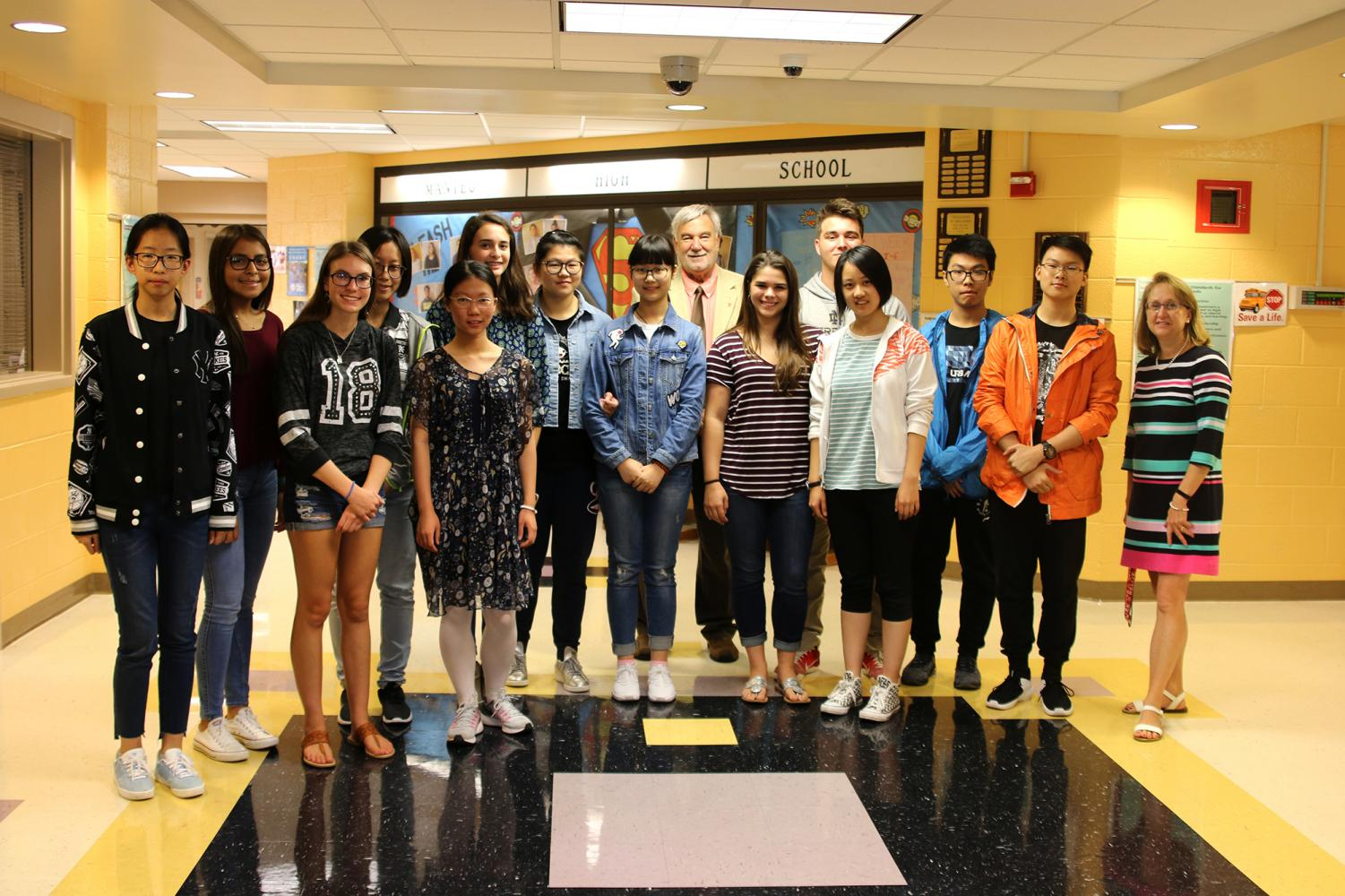Principal John Luciano greets Chinese exchange students and student members of their host families.