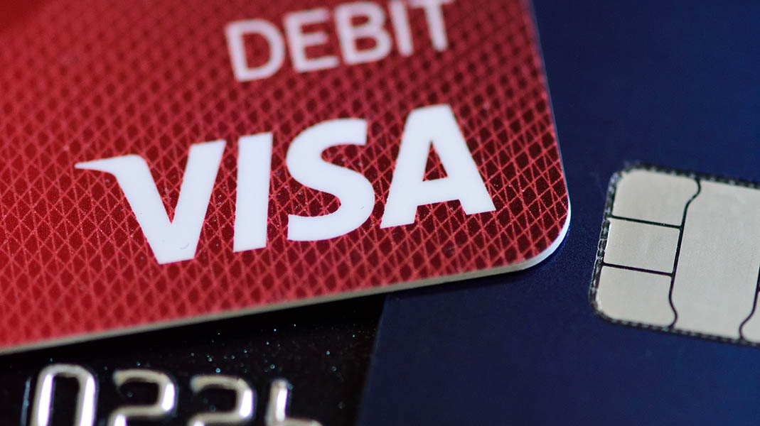 A Visa debit card is pictured with a chip-enabled card in Portland, Ore., on May, 12, 2016. Retail giant Walmart is suing Visa due to the request from the financial company that signatures should still be allowed at the retailer to validate payments. (Alex Milan Tracy/Sipa USA/TNS)