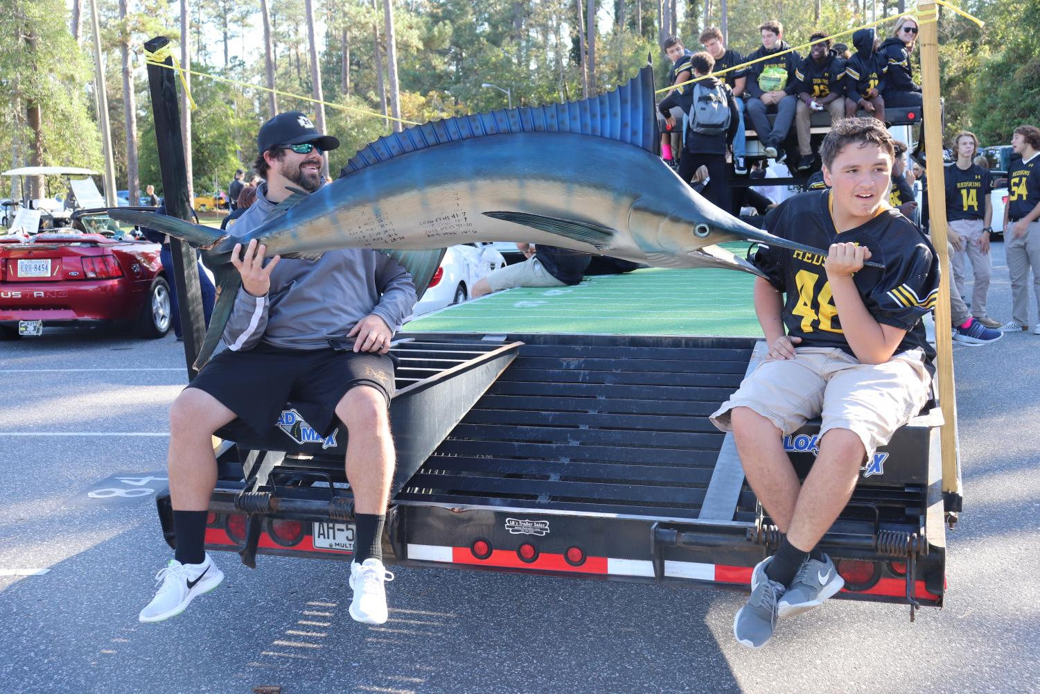 Unidentified man and Josh Sexton carry the marlin trophy in the homecoming parade.